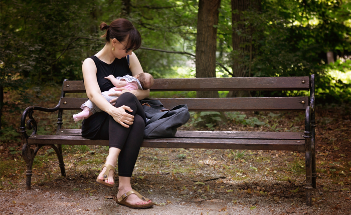 Photo of a woman breastfeeding her baby on a bench in a park.